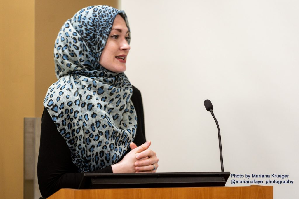 Shannon Al-Wakeel of the Muslim Justice League speaks in front of a microphone.